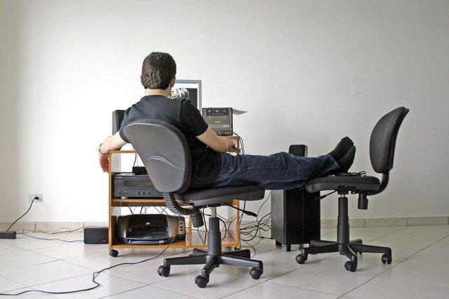 Muž v bílé místnosti se stolem a počítačem, nohy má na vedlejší židli, pracuje