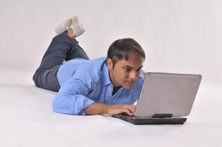 muž ležící u počítače