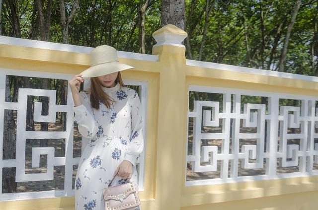 Žena v klobouku stojící u plotu s kabelkou v ruce