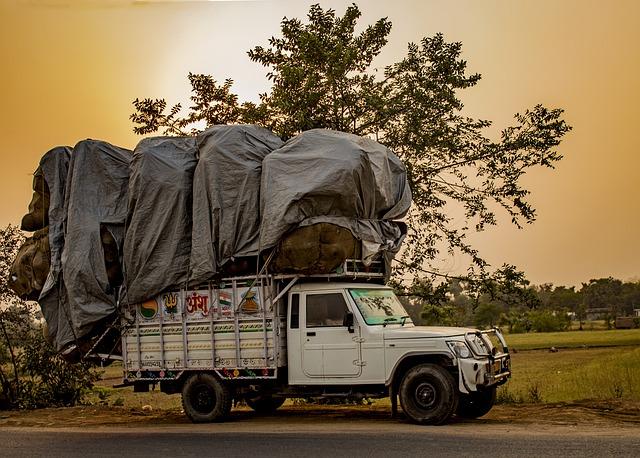 bílý nákladní automobil jede po cestě plně naložen ještě na korbě až po vrch nákladem, který je zakrytý plachtou